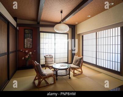 A modern Japanese-style room (washitsu, tatami room), with shoji screen doors (Japanese paper doors) and tatami mats. Shibuya, Tokyo, Japan. - Stock Photo