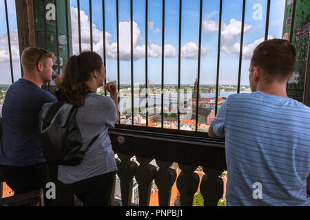 Riga tourists, rear view of three young tourists (18-25) looking down on Riga Old Town from within the viewing platform inside St Peter's Church tower. - Stock Photo