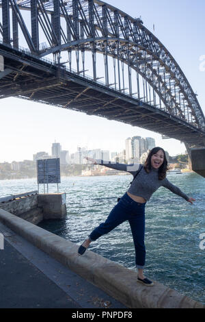 20 May 2018 : Sydney, Australia : young woman walking along the road with the iconic harbour bridge in the background - Stock Photo
