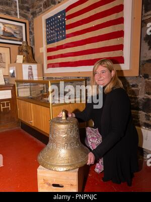 Islay, UK. 22nd September 2018. The ship's bell belonging to the SS Otranto which was sunk in Machir Bay off the coast of the Scottish island of Islay has gone on display in the Museum of Islay Life in Port Charlotte.    Pictured: Museum manager, Jenni Minto with the bell of the SS Otranto. In the background is a flag that has been loaned to the museum by Credit: Rich Dyson/Alamy Live News - Stock Photo