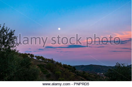 Axarquia, Andalusia, Spain, 22nd September 2018. Spain weather: Wispy clouds create a stunning colourful sunset over the Axarquia mountains on another hot day. An almond tree grove lines the hillside horizon with the nearly full waxing moon visible in the night sky - Stock Photo