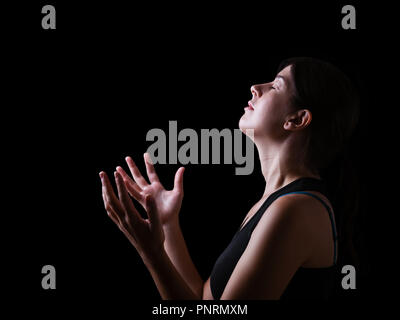 Low key of a faithful woman praying and feeling the presence or being touched by god. Arms outstretched in worship, head up and eyes closed in religio - Stock Photo