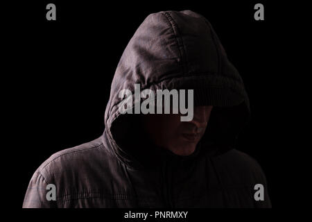Scary and creepy caucasian or white man hiding in the shadows, with the face and identity hidden with the hood, and standing in the darkness. Low key, - Stock Photo