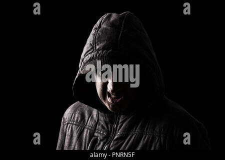 Very angry and aggressive man hiding in the shadows, with the face partly hidden with the hood, and standing in the darkness. Low key black background - Stock Photo