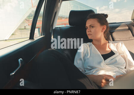 Modern Woman Sitting In Rear Seat Of Car On Road Trip Relaxing - Stock Photo