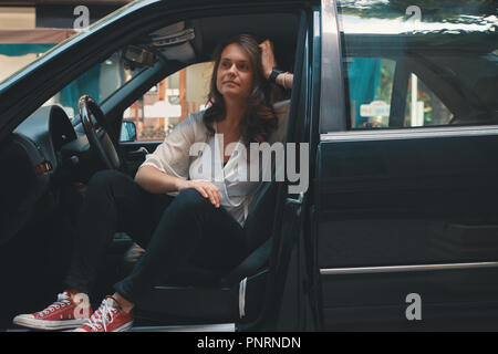 Relaxed woman on city road trip travel leaning out car window on old building background. - Stock Photo