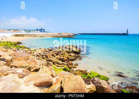 Rocks on sea coast and view of beach in Tarifa town, Costa de la Luz, Spain - Stock Photo