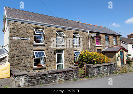 Swansea, UK: July 07, 2018: Street view of typical double fronted terraced house in a Welsh village. Summertime with garden flowers and blue sky. - Stock Photo