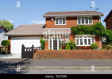 Swansea, UK: July 07, 2018: Four bedroom detached house on a housing estate. Typical 1980's design with attached garage and front garden. - Stock Photo