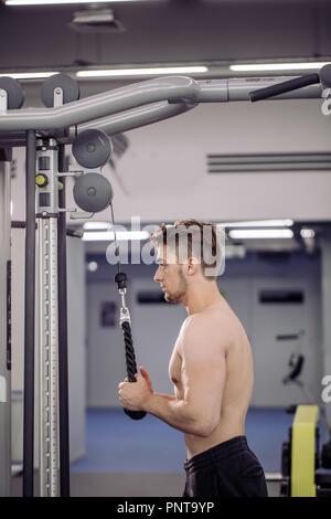 bodybuilder performing exercise with gym training mashine - Stock Photo