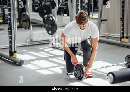 Muscular man putting heavy plates on barbell during workout in gym - Stock Photo