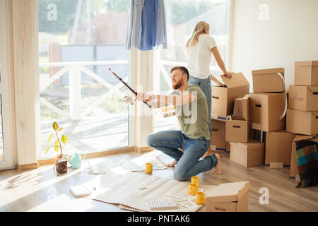 couple is having fun in home with cardboard boxes in new house at moving day - Stock Photo