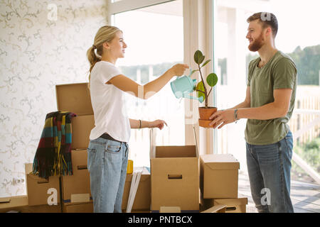 couple unpack boxes in new home. Woman giving flower to her husband - Stock Photo