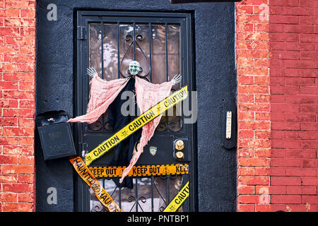halloween decorations including a witch and decorative police stripes on the front door of a house