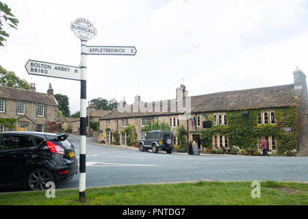 The village of Burnsall, a centre for walking in Upper Wharfedale, Yorkshire, UK, with the Red Lion Hotel in the background - Stock Photo