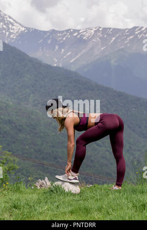 Exercising fitness woman doing exercises in nature. Fit female Asian Caucasian athlete sport model - Stock Photo