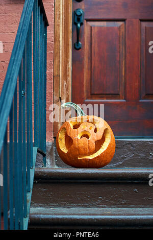 Carved Halloween pumpkins or jack o'lantern on the doorstep in Brooklyn - Stock Photo