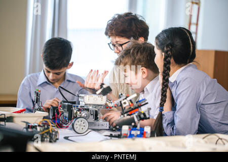 Happy children learn programming using laptops on extracurricular classes - Stock Photo