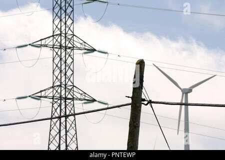 Close up of three different types of energy, old electric post, modern electric post and wind turbine. - Stock Photo