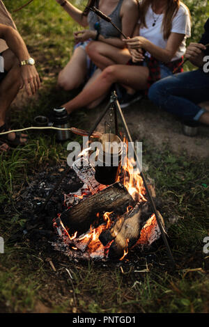 water is boiling in the backet on the bonfire - Stock Photo