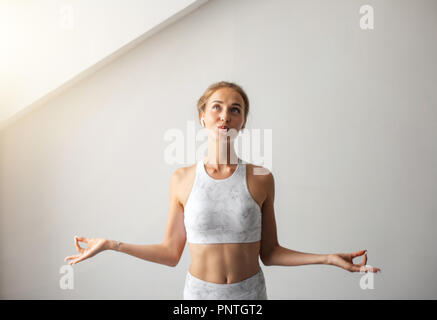 Young blonde woman dressed in white tank top keeping fingers in mudra gesture - Stock Photo