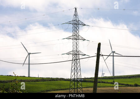 Horizontal view of three different types of energy, old electric post, modern electric post and wind turbine in summer green landscape. - Stock Photo