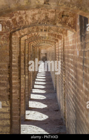 Perspective of the ancient stone arches of the Si o Seh Pol bridge on the afternoon in Isfahan, Iran. Also known as Allahverdi Khan Bridge, or 33 span - Stock Photo