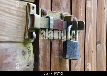 Rusted old padlock on hasp. Vintage lock protecting a wooden door. - Stock Photo