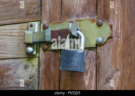 Rusted old padlock on latch. Vintage lock protecting a wooden door. - Stock Photo