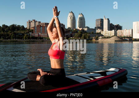 Woman practicing sitting variation of yoga pose on paddle board - Stock Photo