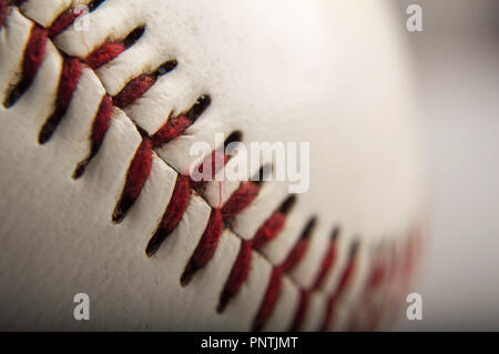 close-up macro of a baseball with red stitching - Stock Photo