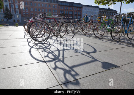 Bicycles for sale on Israels Plads, Israel's Square, Copenhagen, on a Saturday flea market. Long shadows of backlit bicycles. Assembled in  background - Stock Photo