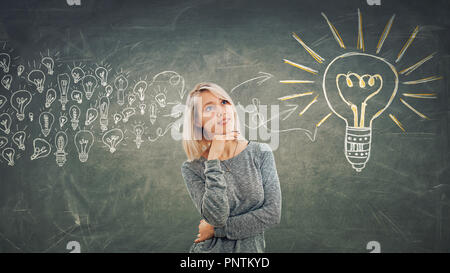 Business concept as a pensive girl with hand under chin, thinking gathering ideas into a big light bulb. - Stock Photo