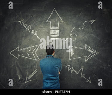 Rear view of pensive businessman thinking in front of a huge blackboard with arrows pointed to different directions. Difficult choice, decide which wa - Stock Photo