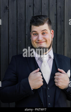 Bridegroom is standing in front of a wooden wall - Stock Photo