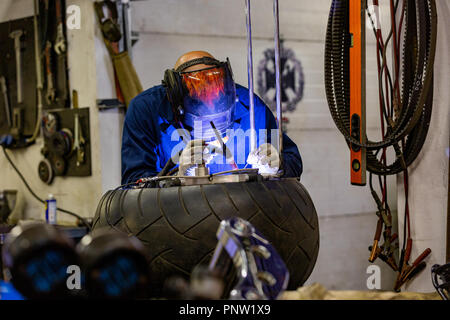 Professional car mechanic working in auto repair service on argon gas cutting machine - Stock Photo