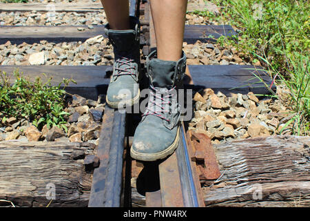 Person is walking with hiking boots over railroad tracks - Stock Photo
