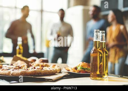Pizza time. Close-up of tasty pizza on the table, with a group of young smiling people resting - Stock Photo