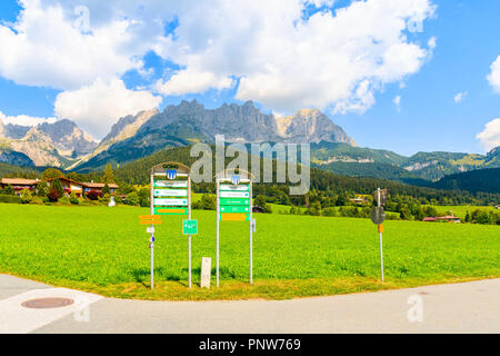 TYROL, AUSTRIA - JUL 29, 2018: Walking and cycling signs on road in Going am Wilden Kaiser mountain village on sunny summer day. This place is most be - Stock Photo