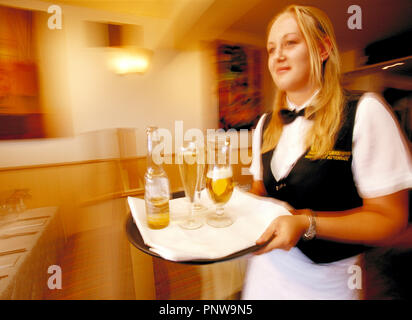 Young blond woman waitress with drinks tray in café restaurant bar. - Stock Photo