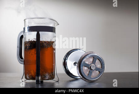 Smoke from hot tea in the tea press container, viewed from above. - Stock Photo