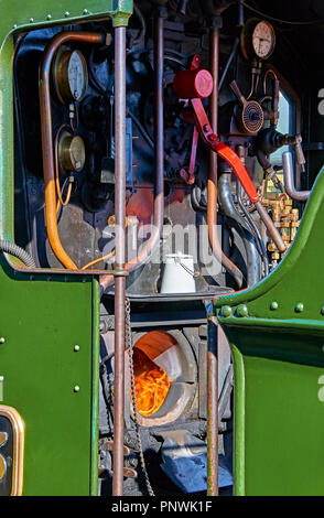 View into the driver's compartment of a fully restored working steam locomotive, showing flames burning in the firebox - Stock Photo