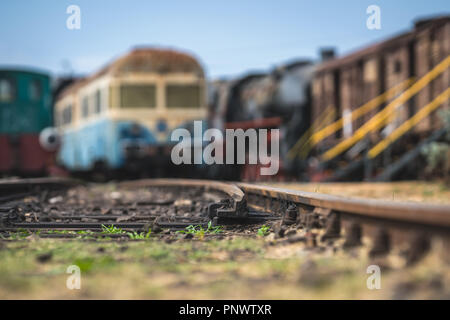 Shallow depth of field closeup of the rail tracks with old disused locomotives and carriages in the background - Stock Photo