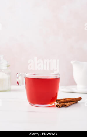 Fruit tea in a glass cup with cinnamon, sugar and milk jug on marble table top with feminine rose background. Copy space. - Stock Photo