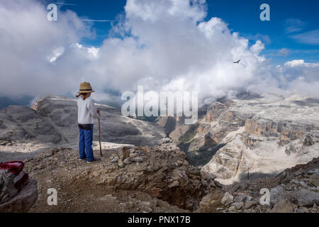 Young child overlooking the landscape on top of the Sella Group massif, with lone buzzard in the sky - Stock Photo