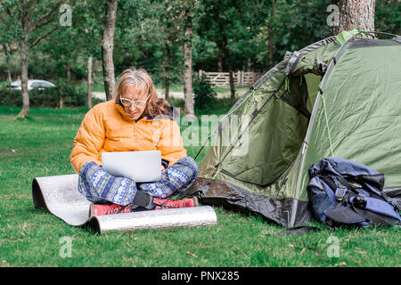 Casually dressed man working on his laptop, on campsite in rural uk.Mobile internet access allowing people to work in remote location.Person using tec - Stock Photo
