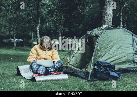 Casually dressed man working on his laptop, on campsite in rural uk.Mobile internet access allowing people to work in remote location. - Stock Photo