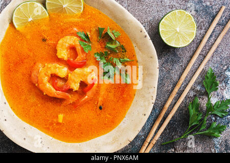 Spicy sour soup with prawns (Tom Yum Goong) on a rustic background. Thai food. View from above, flat lay - Stock Photo