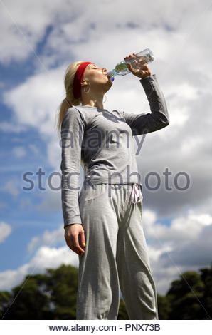 Blonde woman in a tracksuit excercising and drinking water from a bottle - Stock Photo