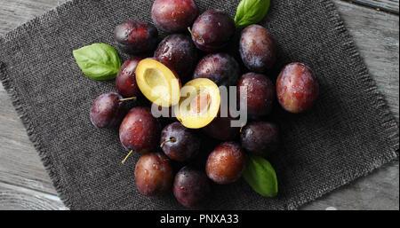 Served ripe plums on napkin - Stock Photo